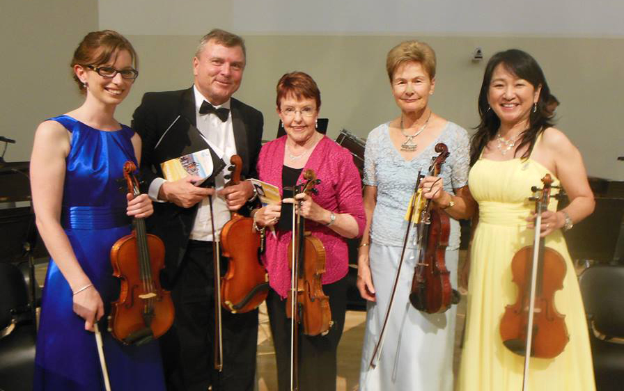 "The 2nd violin section posing for a photo at ""Portraits""."
